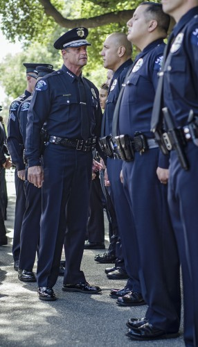 La Verne Police Chief Scott Pickwith walks down the line inspecting his officers' uniform requirements Tuesday morning. The entire force, including sworn police officers, parking enforcement personnel, and senior patrol volunteers, gathered to take a department photograph in the middle of Third Street between Sneaky Park and the Public Safety facility. / photo by Zachary Horton
