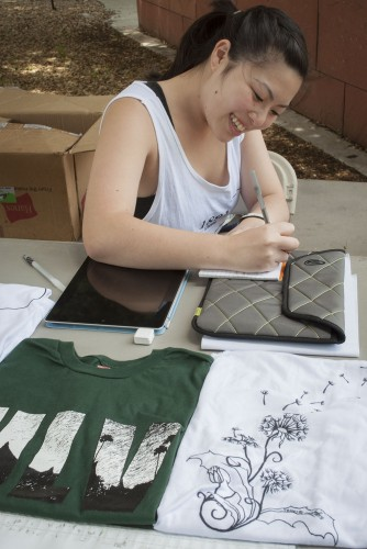 Tiffany Fujioka, a senior business administration major, sells Reverie Outfitters clothing May 15 in front of the Campus Center. The Outfitters is a clothing company created as part of the Integrative Business Practicum. Reverie Outfitters will be selling products again next week. The group's Facebook page, facebook.com/ReverieOutfitters, will announce exact dates and times. / photo by Katherine Careaga