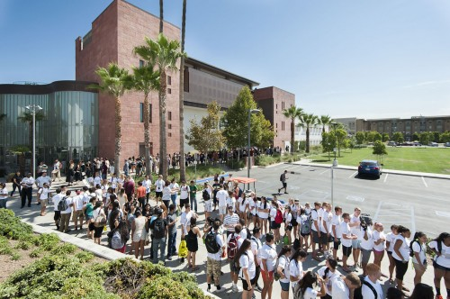 Standing in their assigned groups in the hot August sun, freshmen await their entrance onto Frantz Athletic Court to be welcomed to the University. / photo by Hunter Cole