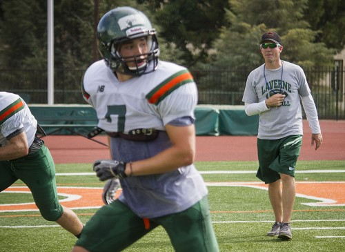 As the season approaches head football coach Chris Krich pushes his team during practice. David Kain (No. 7), a junior safety, runs to block another player during the drill. / photo by Celine Dehban