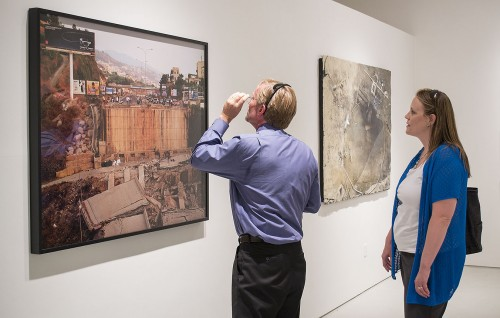 """Jonathan Reed, dean of the College of Arts and Sciences, walks with Kathleen Weaver, assistant dean of the College of Arts and Sciences, through the Harris Art Gallery exhibition, """"Out of Rubble"""" curated by Susanne Slavick. The photograph of the remains of the Halat-Fidar Bridge, north of Beirut, Lebanon, was made by Simon Norfolk in 2006. / photo by Sarah Golden"""