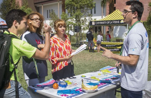 Freshman Resident Housing Association member Garrett Hoffman quizzes students on proper laundry settings at CAB's Health and Fitness Fair Sept. 19. David Vorobyov, junior, celebrates after winning a shirt by answering the questions correctly. RHA was promoting good mental and emotional health along with cleanliness for first-time college residents. / photo by Celine Dehban