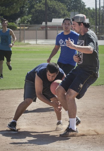 Junior Daniel Gonzalez tries to make an out at third base as Cal Poly Pomona junior Robby Gamble strides in safely at Sigma Kappa's kickball tournament Sunday. Gonzalez and teammate Chris Gonzalez played for Phi Delta Theta's B team, which lost to Gamble's Phi Kappa Tau team. / Photo by Stephanie Ball