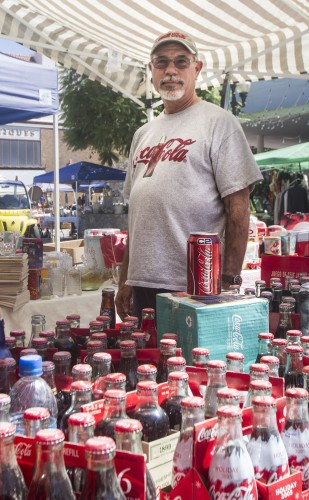 Thomas Stricklin has been a Coca-Cola memorabilia collector since his sister gave him a painted Coke bottle as a vase before he went to college in 1969. He displays his collection at the Collectors' Fair in downtown Pomona on Saturday. / photo by Celine Dehban