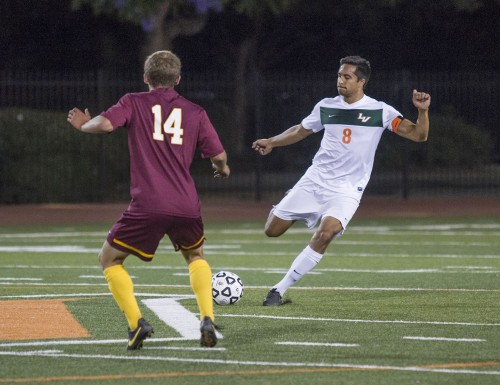 Senior defender Andrew Greenen drives toward the Claremont-Mudd-Scripps side in an effort to stop CMS player Alex Censullo from taking it to La Verne's goal during the first half at Ortmayer Stadium Saturday. The Leopards lost to the Stags, 3-0. / photo by Celine Dehban