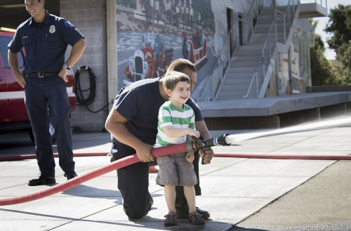 Victor Castaneda, a second year in the fire fighting academy at Mt. SAC, guides 3-year-old Asher Baker in spraying a hose at balloons at the Public Safety Open House Saturday. Baker is the son of Aaron Baker, assistant professor of psychology at the University of La Verne. The open house was held along D Street where police cruisers lined the streets open for anyone to sit in for a tour. / photo by Uyen Bui