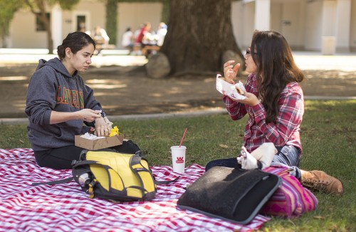 Junior biology major Vivian Aceves and junior mathematics major Allison Jimenez enjoy their free Wienerschnitzel lunch Tuesday on one of the picnic blankets spread out by the Campus Activities Board in Sneaky Park. A Wienerschnitzel food truck and an ice cream truck provided free food for Circus Day as a part of Homecoming Week. / photo by Nicole Ambrose
