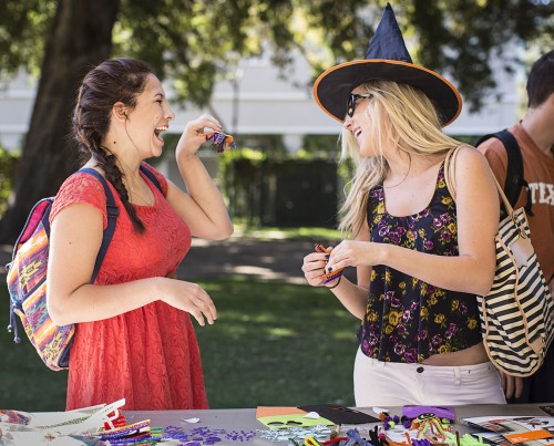 Vanessa Canales, junior history major, shares her Halloween creation with Shelbi Knudsen, senior history major, at the Witch Will You Wear event, hosted by the Campus Activities Board, in Sneaky Park Oct. 17. Students were invited to create Halloween accessories. / photo by Nicole Ambrose