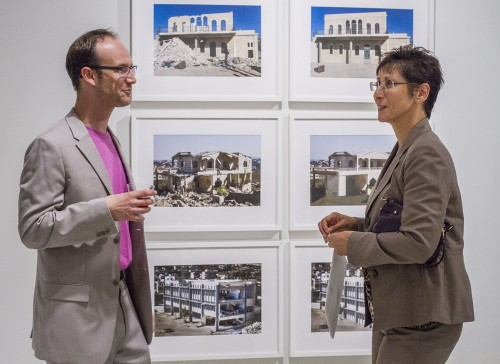 "Dion Johnson, director of University art galleries, tours ""Out of Rubble"" in the Harris Gallery with Myra Garcia, vice president for advancement, at the reception Tuesday. This photo series, ""Repairing Lebanon"" by Lenka Clayton, shows ruined buildings from the 2006 conflict with Israel. Clayton had no idea what the buildings looked like before destruction, so she digitally altered them to look new and untouched by war. / photo by Celine Dehban"