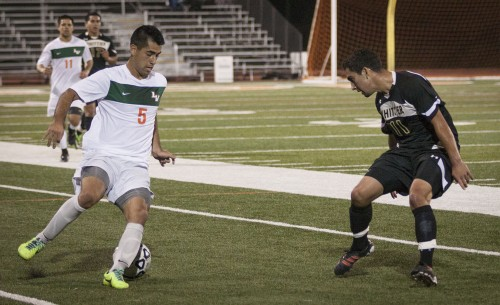 Senior midfielder Ryan Estrada runs the ball down the field attempting to keep it from Whittier's sophomore forward Pablo Gomez in the first half of the game. The Leopards lost the game to the Poets 2-1 in overtime. / photo by Stephanie Ball