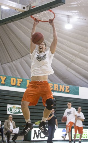 Junior center Niall Harrison competes in a slam dunk contest against his basketball teammates. This was one of many contests preformed as a part of Moonlight Madness at Frantz Athletic Court Oct. 24. Hosted by CAB, the event kicks off the upcoming basketball season. / photo by Nicole Ambrose