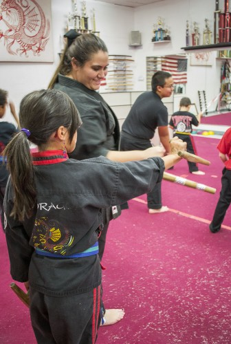 Senior Ava Jahanvash demonstrates the basics of the Tonfa to a martial arts student in preparation for an upcoming competition. Jahanvash teaches karate at her family's Martial Arts Studio, Red Dragon Karate, in Diamond Bar every Thursday at 5 p.m. / photo by Sarah Golden