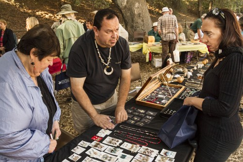 Michael Bracamontes sells traditional Tongva jewelry to Ceeroosha Andreas at the Rancho Santa Ana Botanic Garden Acorn Festival Saturday. Bracamontes makes the jewelry and sells it with the help of and his mother, Dlia Bracamontes. Andreas returned to the festival on the second day to buy some more earrings from them. The festival celebrated the traditional harvest season for the Tongva tribe, for whom the acorn is a staple in their diet. The 13th annual acorn festival was held Nov. 16 and 17. / photo by Ryan Gann