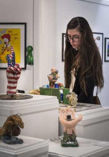 """Claremont High School senior Melanie Gettler browses her friends' and classmates' artwork in the """"ArtReach 2014: The Art of Pop Culture"""" exhibit, staying to look at other art by other local high school students. All of the art commented on pop culture, the effects or the obsession with it. The exhibit will be on the Millard Sheets Center for the Arts at the Fairplex until March 19. / photo by Helen Arase"""