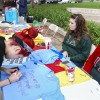 Junior Bonita Estrada decorates a shirt for Iota Delta sorority's Clothesline Project with sophomore Katie Lewis, and senior Amanda Timko at the booth. The demonstration focuses on raising awareness and prevention of violence towards women.  Students decorated a colored shirt at the table, each of which represents a different atrocity committed towards women. The shirts were then hung up on a clothesline with their messages displayed. / photo by Julian Burrell