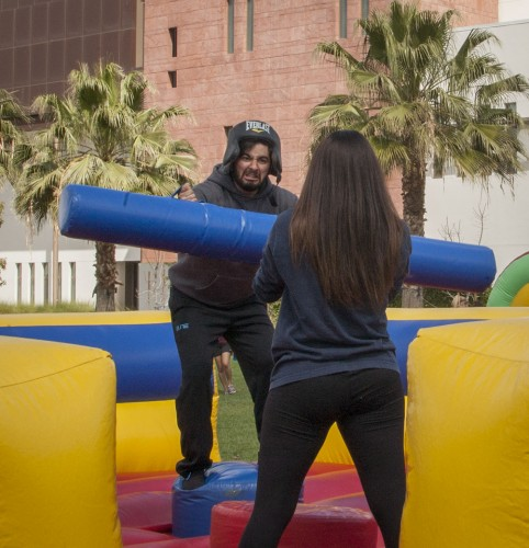 """Tatiana Raygoza, a sophomore kinesiology major, and Arian Avila, a junior kinesiology major, enjoy the bounce houses at the CAB event """"Play for a Cause"""" to raise awareness about Tourette's Syndrome. CAB Special Events chairman Tyler Bertao was inspired to plan the event because his brother has Tourette's and he wants to help dispel rumors about the disorder. / photo by Katie Madden"""