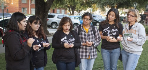 Kim Navarro, One in Three Club president; Sandy Maas, club vice president; Rebekah Reza, senior psychology major; Roxanna Bautista, sophomore psychology major; Lili Gradilla, intercultural program coordinator; and Loretta Rahmani, dean of student affairs, hold a candlelight vigil Friday in honor of victims of sexual violence and abuse. The vigil was part of Take Back the Night, an event One in Three hosted to raise awareness about sexual assault and to offer support to victims. / photo by Katie Madden