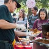 Emily Aguirre, senior sociology major, orders a chili hot dog from Silvestre Rojas at Sneaky Park Tuesday. Students lined up for free Pink's Hot Dogs as part of Letters in the Park. Hosted by Greeks, the event aimed to raise breast cancer awareness. / photo by Mariela Patron