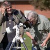 Chairman and Professor of Theatre Arts David Flaten watches Chairman of the Mathematics-Physics-Computer Science Department and Professor of Mathematics Michael Frantz observe the partial solar eclipse on Thursday, Oct. 23 in the University Quad. The Physics department set up camp with telescopes, solar filters and a projector for a few hours and invited anyone who walked by to view the moon partially obstruct the sun. According to BJ Haddad, Physics Lab Manager, it is very rare to see a solar eclipse. / photo by Helen Arase