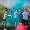 "Julie Ordoñez ambushes a friend with teal color during a dance party after completing the Color Run Saturday at the Fairplex. When crossing the finish line, participants were given one packet of color but could collect more from the stage by joining in dance competitions. ""The Happiest 5K on the Planet"" is an untimed race that promotes healthiness and happiness. Each ""color runner"" is sprayed with paint at each kilometer. / photo by Helen Arase"