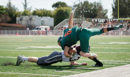 La Verne senior wide receiver Andres Fernandez is tackled by Redlands sophomore defensive back Aaron Mandell Saturday at the Homecoming Game. The Bulldogs took a bite out of the Leopards' pride as the Leopards fell, 64-28, at Ortmayer Stadium./ photo by Emily Bieker