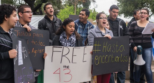 """Sophomore Marvin Tapia, sophomore Jose Rios, senior Christian Moore, junior Chrishelle Bates, senior Gerardo Cuevas, sophomore Rochelle Munoz, junior David Garibay, and junior Abril Camarena chant at the """"Solidarity of the 43"""" protest in Sneaky Park. Camarena organized the event to bring attention to the 43 male college students who were handed over by the police to a Narc gang Sept. 26 in Iguala, Guerrero Mexico. Jose Calderon, Professor Emeritus of Sociology and Chicano/a-Latino/a Studies at Pitzer College, led the protest Wednesday. / photo by Sonora Hernandez"""