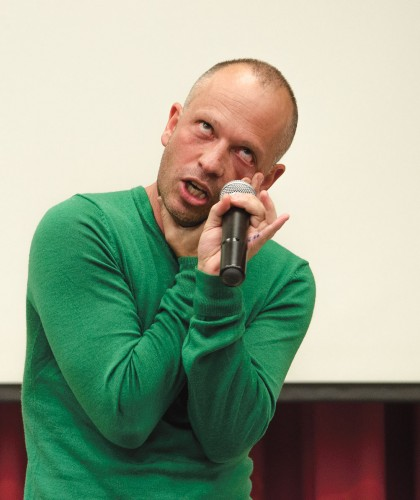 Daniel Packard, love expert, presented love advice Feb. 12 in LaFetra Lecture Hall. As part of his routine, Packard portrayed a woman putting on eyeliner. Packard used a thin strip of blue tape to separate the men and women who attended. / photo by Alexandra Arkley