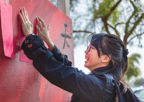 "Sarah Tang, sophomore broadcasting major, catches and reattaches fortunes of other students on a temporary wall at the South Quad during a gust of wind Feb. 19 at the Chinese New Year event planned by Campus Activities Board, International Student Organization and Chinese Students and Scholars Association. ISO set up stations for students to make lanterns, learn about their personalities based on their birth year and take fortune bags for good luck. Tang wrote, ""Hope you ascend higher"" on her fortune. / photo by Helen Arase"