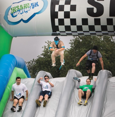 "The Insane Inflatable 5K race Saturday at the Fairplex featured several inflatable obstacle courses. Participants started the course climbing inflatable stairs and then sliding down to begin the 3-mile race. Other inflatables included ""wrecking balls."" Funds raised through runners' donations benefit the Special Olympics Southern California.  / photo by Sara Flores"