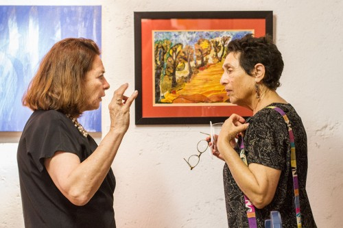 """Artist Rosa Elena Osicka discusses her work with Karen Feuer-Schwager, another artist featured in the 11th annual Women International Exhibit at the Latino Art Museum in Pomona March 14. Osicka's piece, """"My Own Universe – Autumn,"""" is a collage made of embroidery, lace, other fabrics and oil paints. The collage features nine trees, which Osicka has rendered to represent different facets of life. / photo by Celine Dehban"""