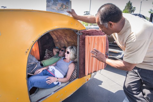 Jerry Maldonado and Diana DeOrio take cover from the heat in a renovated 1946 teardrop trailer, while owner Diamond Williams explains the history of teardrops and how he acquired it for $45 in 1977. Williams completed the restoration himself, allowing the teardrop to be self-sustainable with solar panels and water tanks. Saturday's Auto Tech Car Show at Bonita High School's student parking lot benefited the school's Automotive Technology program. DeOrio's son is a freshman in the program at BHS.  / photo by Helen Arase