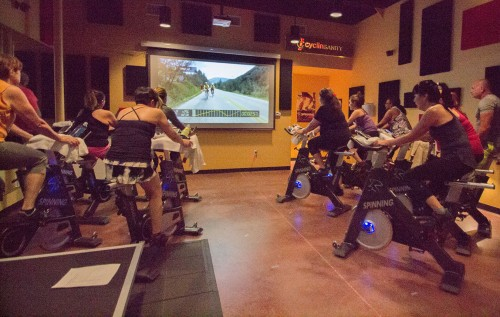The members of Cyclinsanity in La Verne experience virtual cycling presented by epicRIDES. Virtual cycling classes are being introduced at fitness studios around the country. The Thursday class, hosted by Shirin Beckett, was the first class at Cyclinsanity to view locations such as Aspen, Colorado. The Aspen route is a 32 mile ride on Maroon Bells Road and Castle Creek Road. / photo by Jerri White