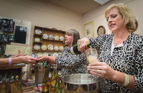 Generations Antiques co-owner Carrie Leeper and friend Tracy Tyra serve sparkling wine in the back room of the store in downtown La Verne Saturday during Sip of La Verne Old Town Wine Walk. Leeper and Tyra served Spanish Sparkling Cava and Almond Sparkling to complement the 679 strawberries they hand-dipped in chocolate and cheese and crackers. This is the third year in a row they have served sparkling wine and strawberries. / photo by Helen Arase