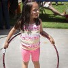 Romina Gomez, age 5, watches her father try to hula-hoop at the 10th annual Family Literacy and Math Conference Saturday at Sneaky Park. Gomez was one of several students ranging from preschool to eighth grade invited to join the event sponsored by the LaFetra College of Education. The goal of the conference was to give parents ideas to help their children succeed. The conference included activity booths for the children. photo by / Celene Vargas