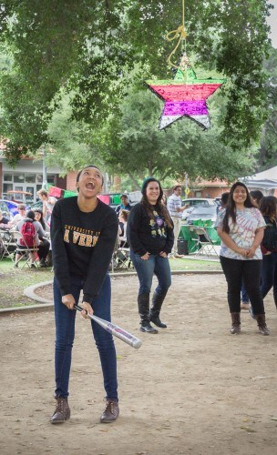 Freshman journalism major Thandi Ware takes a few swings at the piñata during the Cinco de Mayo celebration in Sneaky Park Tuesday. Hosted by the Latino Student Forum, students enjoyed free food, a photo booth, piñatas and DJ music. / photo by Michelle Leon