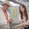 "Jasmine Martinez, senior architecture major at Mt. San Antonio College, explains the design of one of her three projects to George Assenelli, parent of one of the other artists, at the ""Curatorial Studies Selects"" show Monday in the Arts and Communications Building. The exhibit featured work by local artists and students who were selected by the Curatorial Studies class. Martinez used balsa wood, foam and adhesive to recreate the UNESCO laboratory in Vesima, Italy for her piece ""UNESCO Laboratory, West Section Cut."" She liked the steps of the laboratory, as it represented a step into a sustainable environment. / photo by Jolene Nacapuy"