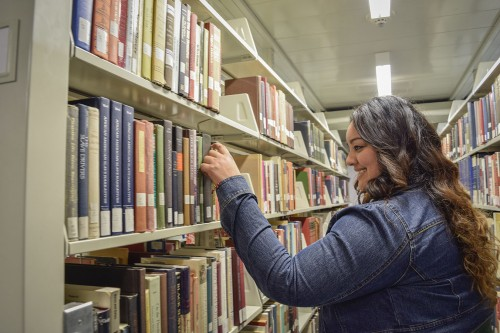Browsing in the history section of the Wilson Library, La Verne alumna Nancy Reyes enjoys reading and learning about new cultures. Reyes graduated with a master's degree in education and spent a year teaching English in China. / photo by Nanor Zinzalian