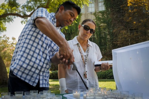 Jose Perez-Gonzalez, professor of modern languages, and Gloria Montebruno Saller, professor of modern languages, make a silent prayer as they light a white candle in honor of the victims of 9/11 at the remembrance event Sept. 11 at the rock. Those who attended were given the option to light a second candle for any personal reasons. After the first candle, Saller lit another, which she said made her emotional as she was reminded of being away from her home in Italy./ photo by Emily Lau