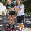 "Senior Kinesiology student Diana Peña, assisted by Junior Education student Noelle Cobb, warily rides a self-balancing scooter, sometimes referred to as a ""hoverboard,"" in the Johnson Family Plaza Thursday, October 1. The scooters, being sold as a project for business and accounting students, have surged in popularity at shopping malls and online stores as videos and articles about the toy have begun to go viral."