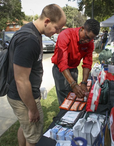 "Wayne O'Bannon of Prep and Save shows sophomore business major Jerrol Guidry the various kinds of emergency kits students can keep in the dorms. Prep and Save, located in Upland, sells emergency supplies for many needs and showcased its many products at the University of La Verne's disaster and preparedness fair Oct. 15 in Sneaky Park. The fair was a part of the Great California Shakeout, an annual event where millions of people across California practice how to ""drop, cover and hold on"" in case of an earthquake. / photo Kristina Bugante"