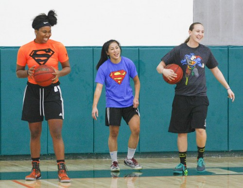 Clad in their superhero themed shirts, women's basketball team members sophomore Kayla Chism, senior Shannon Irwin and freshman Emily Chan prepare to play a basketball relay against the men's team at Moonlight Madness Oct. 22 in the Athletic Pavilion. / photo by Terrence Lewis