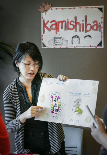 The Japan Daisuki club celebrated the Shichi Go San festival Friday in the Campus Center Ballroom. Senior creative writing major Sandy Hwang explains the Shichi Go San festival to students with kamishibai, a Japanese form of storytelling with pictures.  / photo by Terrence Lewis