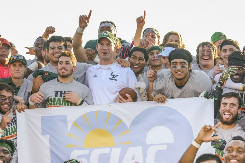 Head coach Chris Krich poses with his players and a SCIAC banner after the game. The Leopards move on to the first round of national playoffs, where they will face the St. Thomas Tomcats Saturday in St. Paul, Minnesota./ Photo by Daniel Torres