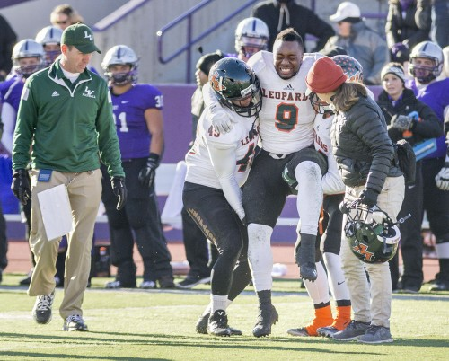 A broken fibula injury ended La Verne junior defensive back Josh Hardy's postseason game in the third quarter against St. Thomas. Head coach Chris Krich, players and trainers ran out to Hardy when the play was stopped. Other injuries included senior starting quarterback William Livingston and junior second-string quarterback Zachary Tomlinson./ photo by Helen Arase