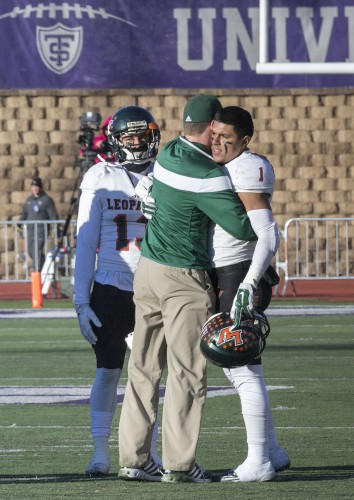 ­­­La Verne junior wide receiver Alex Arellano was one of a few players who remained on the field with head coach Chris Krich after the game. Krich took the opportunity to speak with the players informally, including senior wide receiver Alex Villalobos, who he embraced. The Leopards lost to the Tomcats, 57-14, in the first round of the NCAA Division III Championships, ending their season. This was the first time La Verne played in a postseason tournament in 21 years. / photo by Helen Arase