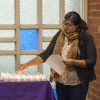 Hasfa Arain, interfaith leader from the Muslim community, helps light candles in remembrance of the lives lost in the San Bernardino mass shooting. The congregation was asked to say a positive human character trait for each candle as the names were read. The vigil was one of many across the country and this shooting was one of 350 mass shootings in the United States in 2015 alone. The vigil was held Dec. 3 in the Interfaith Chapel./ photo by Terrence Lewis