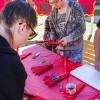 Business administration majors Liang Cui and Melanie Browdy cut red snowflakes during a Chinese New Year celebration on Monday. The Campus Activities Board's event in Sneaky Park celebrated the Year of the Monkey with food, traditional music and various activities. / photo by Kendra Craighead
