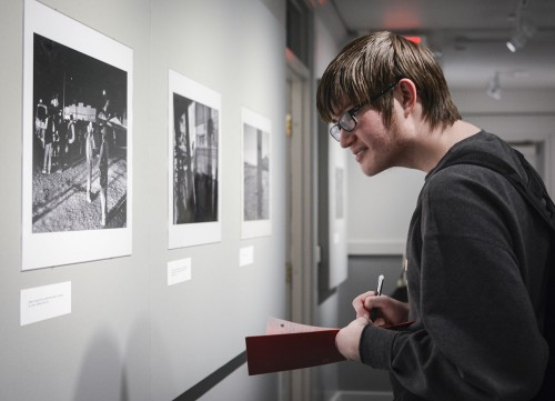 """Freshman history major Jon Hall writes notes for a honors colloquium class discussion on Michael Robinson Chávez's exhibition """"The Driest Seasons: California's Dust Bowl."""" The reception for Robinson Chávez was held Feb. 18 in the Carlson Gallery in Miller Hall. / photo by Daniel Torres"""