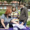 Retired Los Angeles Sheriff's Department Sgt. Bettina Aschen­brenner gives Linda Bartelt, adjunct professor, and John Bartelt, professor of education, purple ribbons that represent domestic violence awareness. Aschenbrenner's House of Ruth table was one four booths set up at the Take Back the Night event March 3 in Sneaky Park. / photo by Emily Bieker
