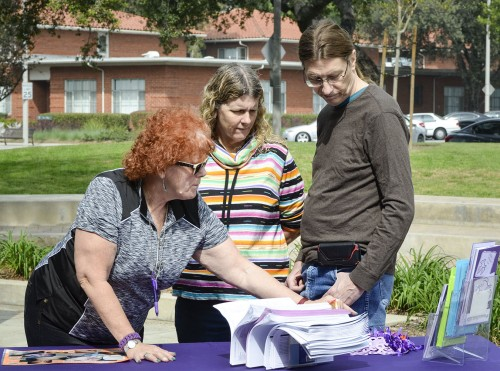 Retired Los Angeles Sheriff's Department Sgt. Bettina Aschenbrenner gives Linda Bartelt, adjunct professor, and John Bartelt, professor of education, purple ribbons that represent domestic violence awareness. Aschenbrenner's House of Ruth table was one four booths set up at the Take Back the Night event March 3 in Sneaky Park. / photo by Emily Bieker